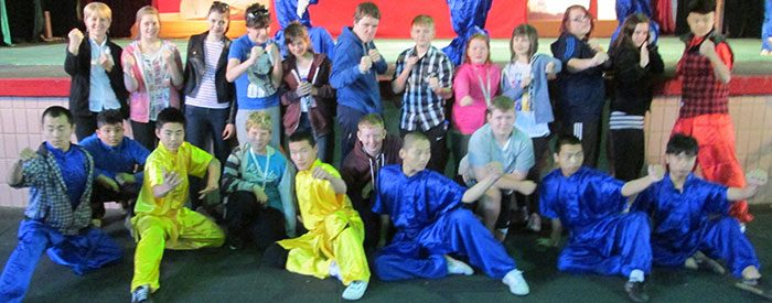 School students taking on a kung fu experience