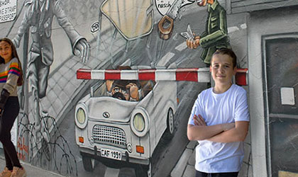 Student standing by the Berlin Wall